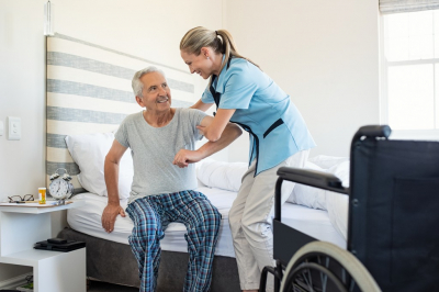 Smiling nurse assisting senior men to get up from bed.