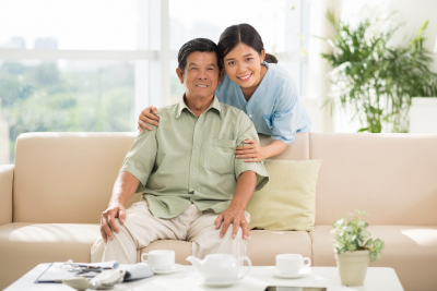 Portrait of smiling Vietnamese doctor hugging senior man
