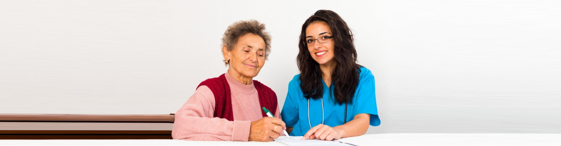 a medical personnel with an old lady writing