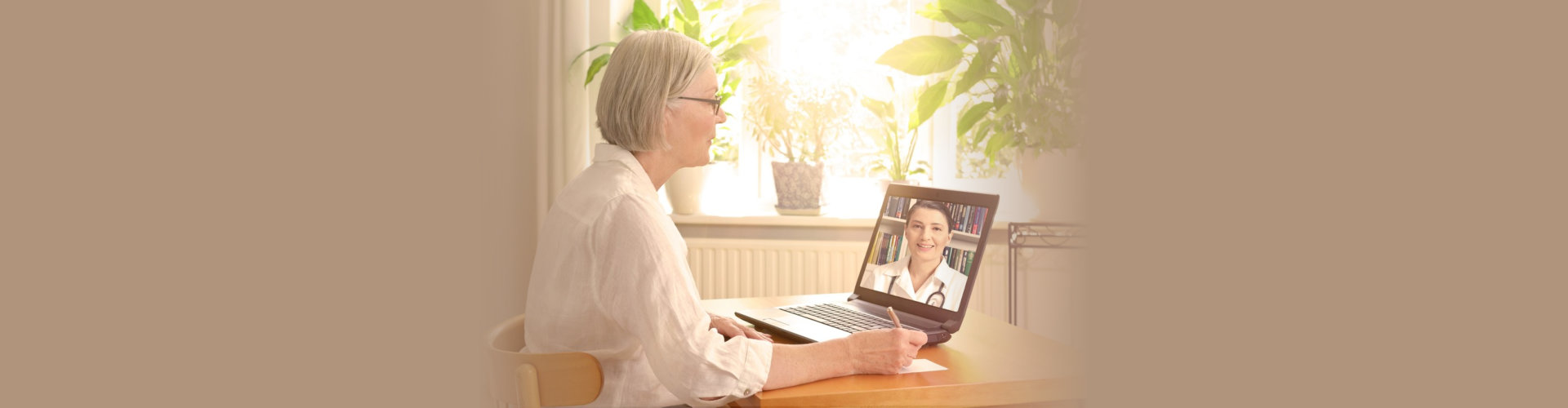 Senior woman in her sunny living room in front of a laptop